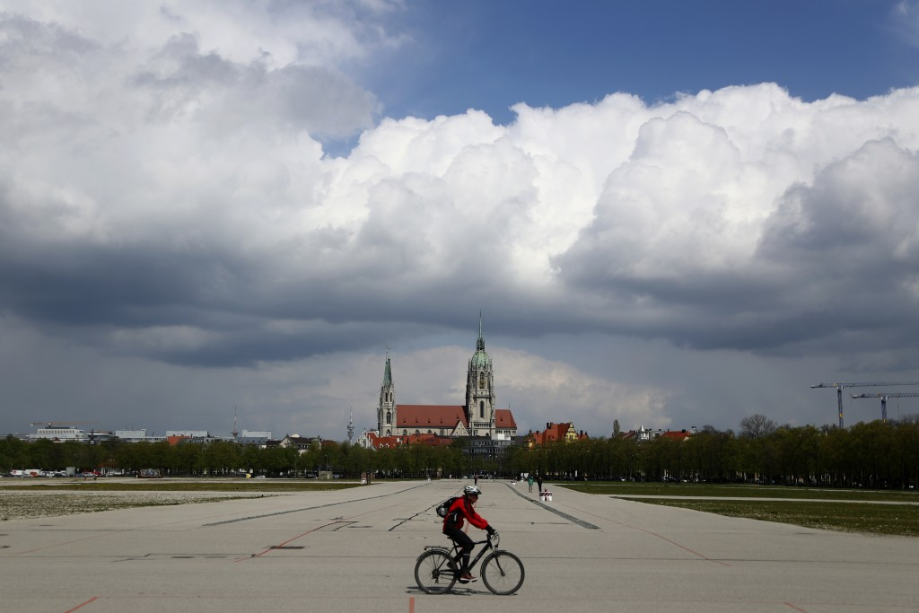 A cyclist crosses the 'Oktoberfest' beer festival area 'Theresienwiese' in front of the St. Pauls church in Munich, Germany, Monday, May 3, 2021. The ...