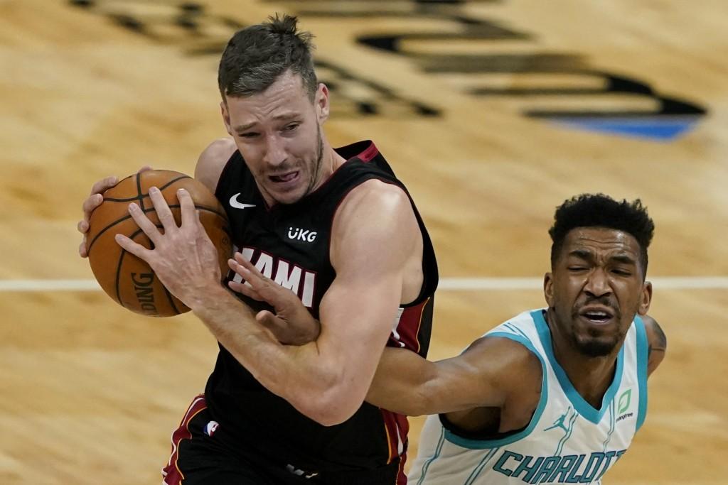 Charlotte Hornets guard Malik Monk, right, fouls Miami Heat guard Goran Dragic during the first half of an NBA basketball game on Sunday, May 2, 2021,...