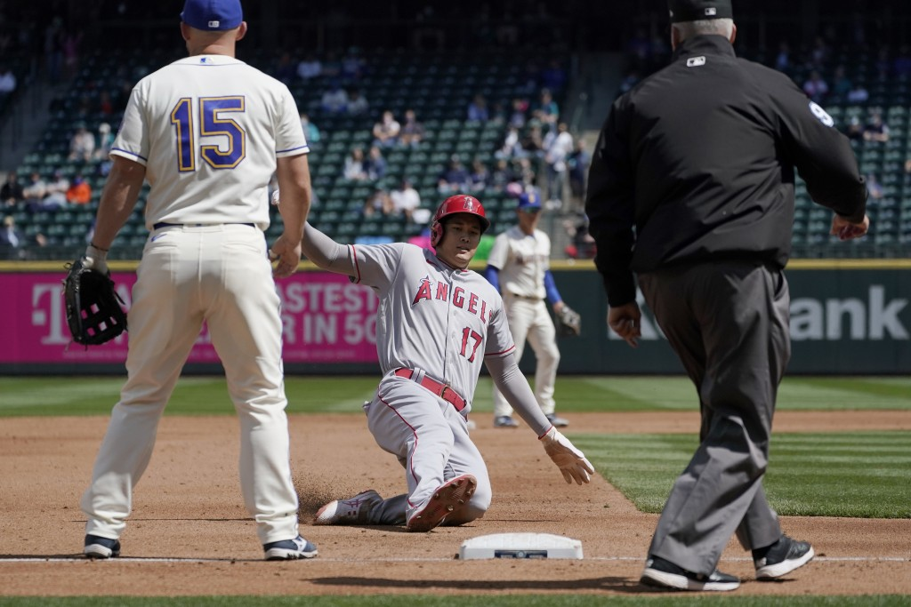 Los Angeles Angels' Shohei Ohtani (17) slides safely into third as Seattle Mariners third baseman Kyle Seager (15) looks on during the third inning of...