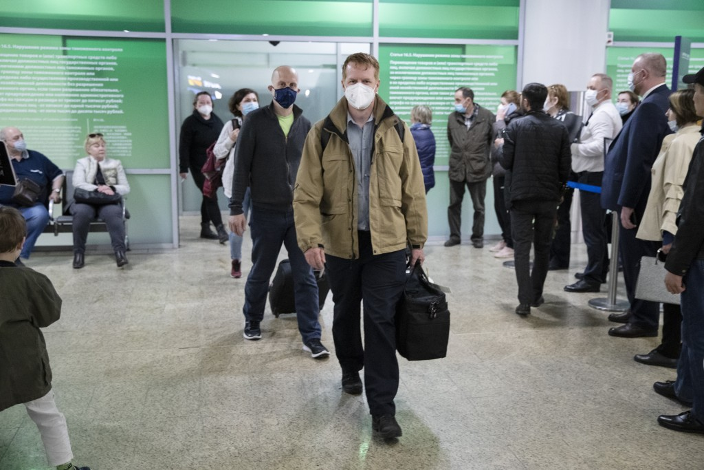 Germany's Enno Lenze, center, and Uwe Keim, center left, both wearing face masks to protect agains coronavirus, enter the hall after arriving at Shere...