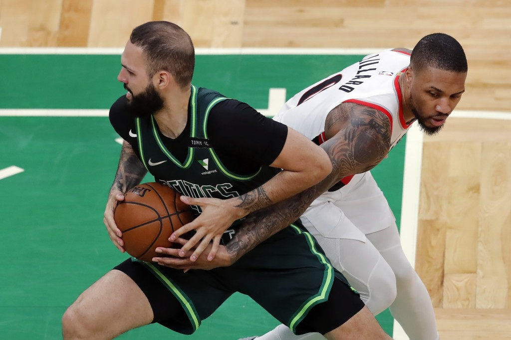 Boston Celtics' Evan Fournier drives past Portland Trail Blazers' Damian Lillard (0) during the first half of an NBA basketball game, Sunday, May 2, 2...