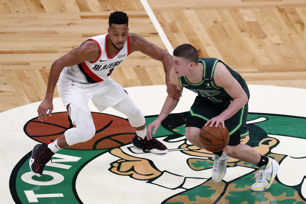 Boston Celtics' Payton Pritchard (11) drives past Portland Trail Blazers' CJ McCollum (3) during the first half of an NBA basketball game, Sunday, May...