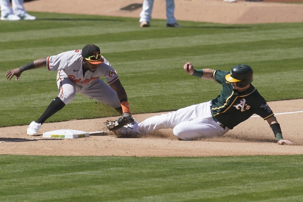 Oakland Athletics' Sean Murphy, right, is tagged out trying to advance to third base by Baltimore Orioles third baseman Maikel Franco, left, during th...