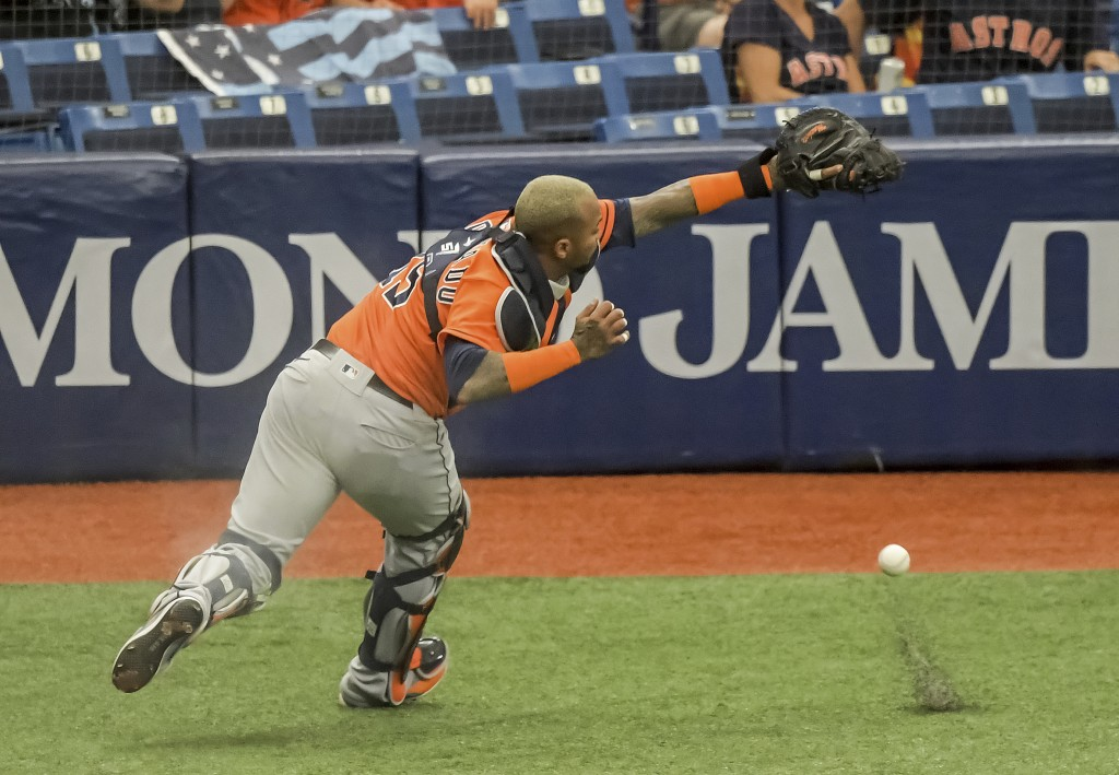 Houston Astros catcher Martin Maldonado chases down a pop fly hit by Tampa Bay Rays' Francisco Mejia in foul territory during the second inning of a b...