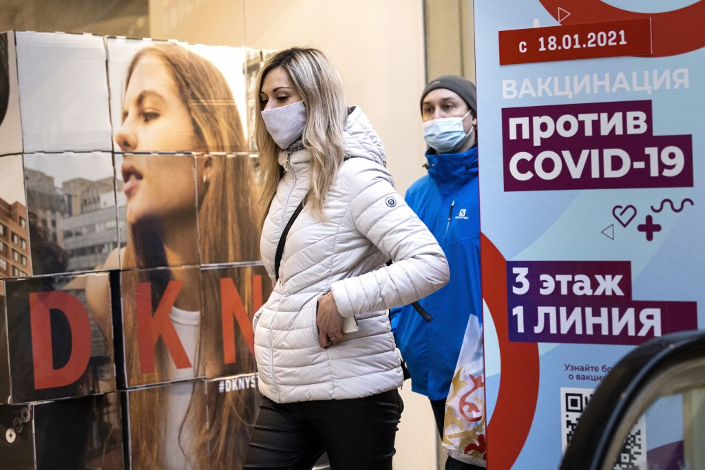 """A woman wearing a face mask to protect against coronavirus walks past a poster reading """"vaccination against COVID-19"""" at the GUM, the State Department..."""