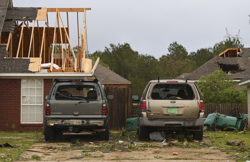 Damaged homes and vehicles are seen along Elvis Presley Drive in Tupelo, Miss., Monday, May 3, 2021. A line of severe storms rolled through the state ...