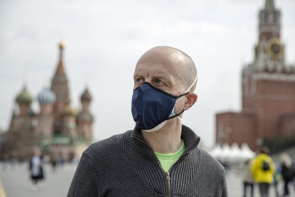 Uwe Keim wearing a face mask to protect against coronavirus walks in Red square after getting the first shot of Russia's Sputnik V coronavirus vaccine...