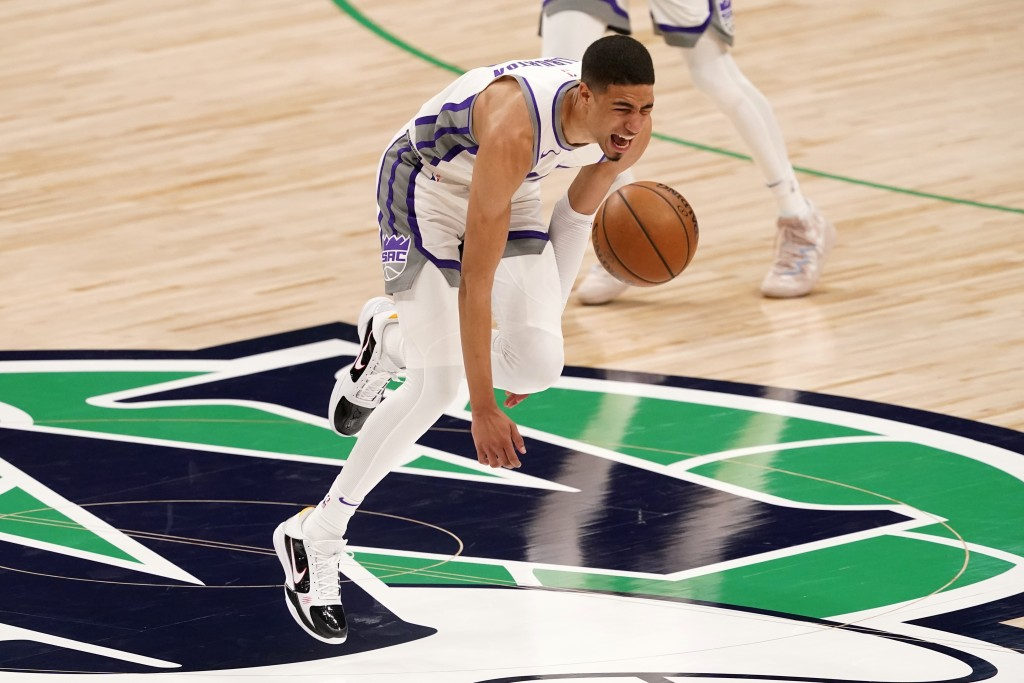 Sacramento Kings guard Tyrese Haliburton (0) loses control of the dribble and falls to the ground after suffering an unknown lower leg injury in the s...