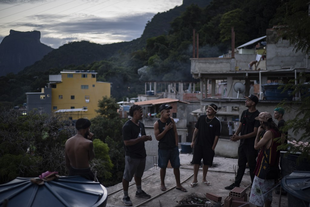 """Trap de Cria artist Vitor Oliveira, known as """"MC Piloto,"""" second left, gathers on the rooftop of his home and recording studio with friends and other ..."""