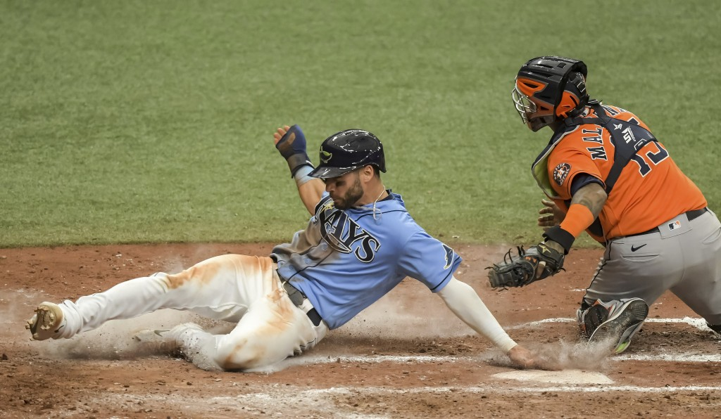 Tampa Bay Rays' Kevin Kiermaier, left, slides past Houston Astros catcher Martin Maldonado, right, to score on Rays' Willy Adames' ground ball to firs...