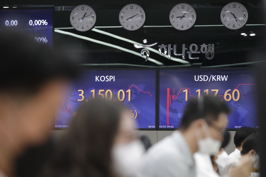 Currency traders work near screens showing the Korea Composite Stock Price Index (KOSPI), left, and the foreign exchange rate between U.S. dollar and ...