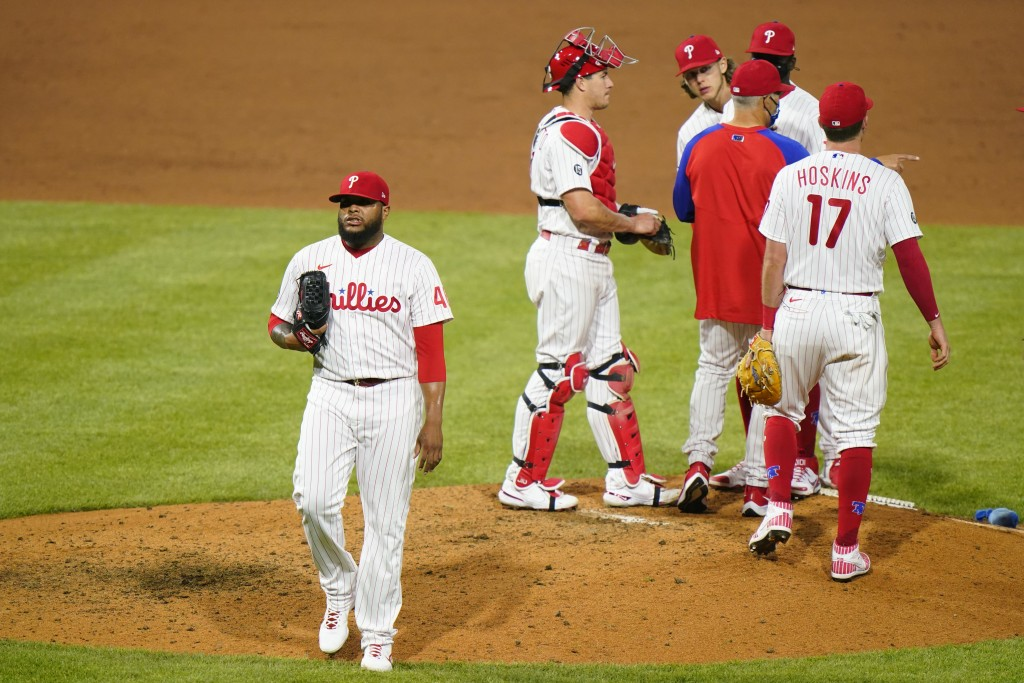 Philadelphia Phillies pitcher Jose Alvarado, left, walks to the dugout after being pulled during the eighth inning of baseball game against the New Yo...