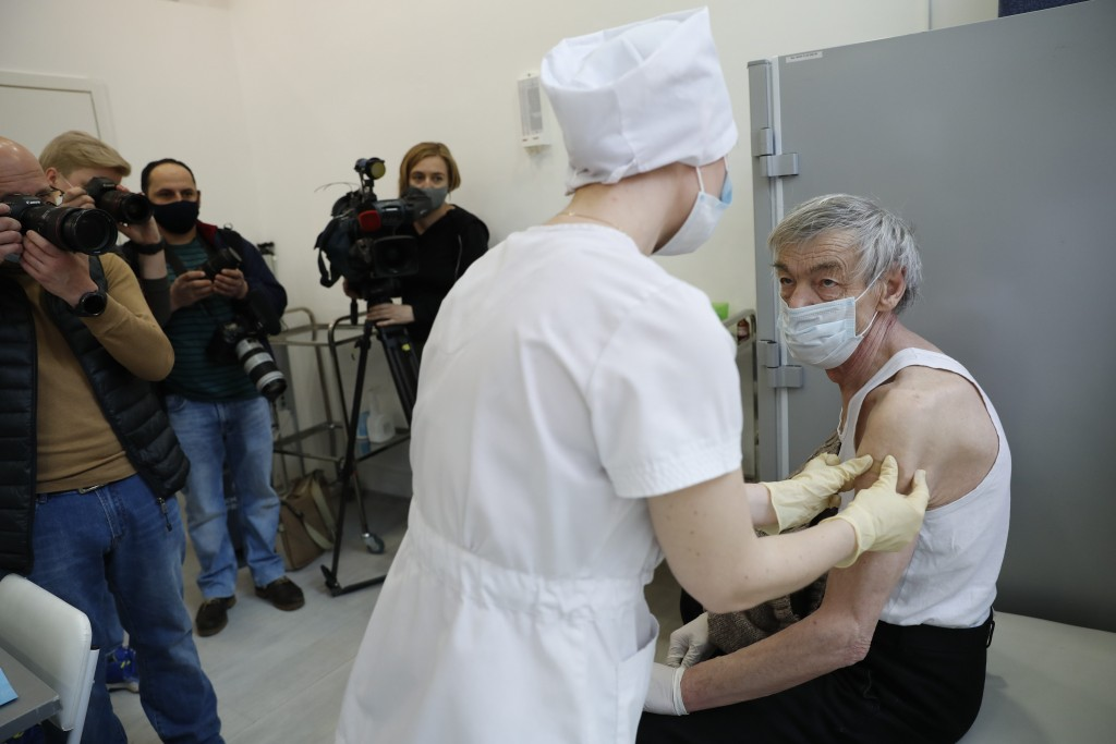 An elderly man wearing a face mask to protect against coronavirus receives a shot of Russia's Sputnik V coronavirus vaccine in front of working visual...