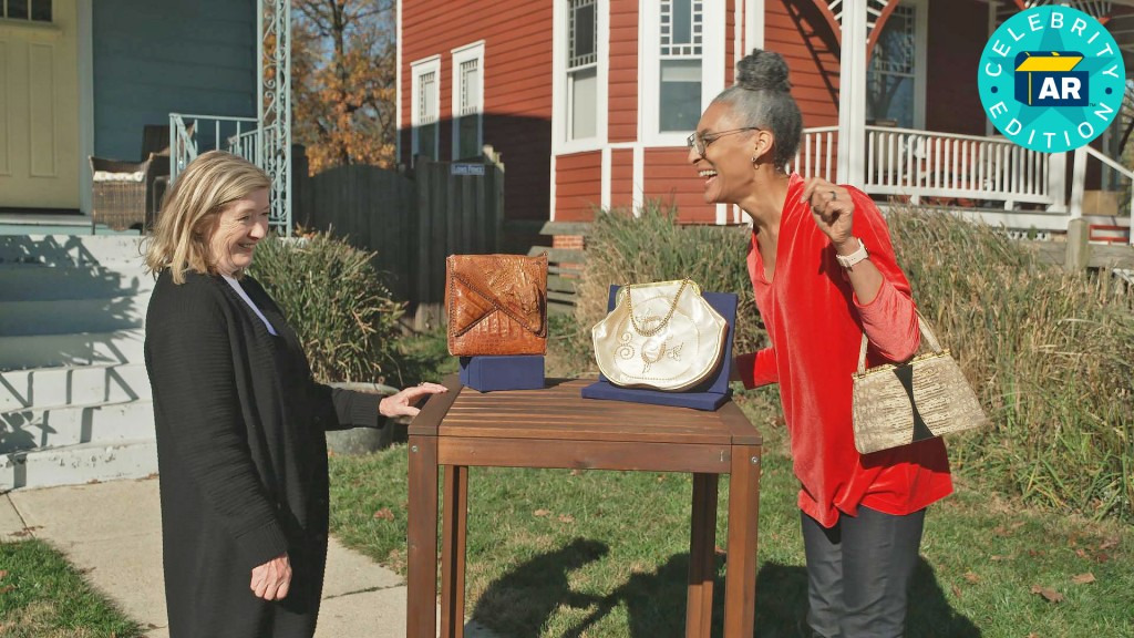 """This image released by WGBH-TV shows Katy Kane, left, as she appraises celebrity chefCarla Hall's vintage purse collection in an episode of """"Antiques..."""