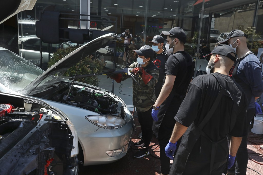 Female Iranian car detailer Maryam Roohani, left, cleans a car spraying water as her trainees watch, at a  detailing shop in Tehran, Iran, Sunday, Apr...
