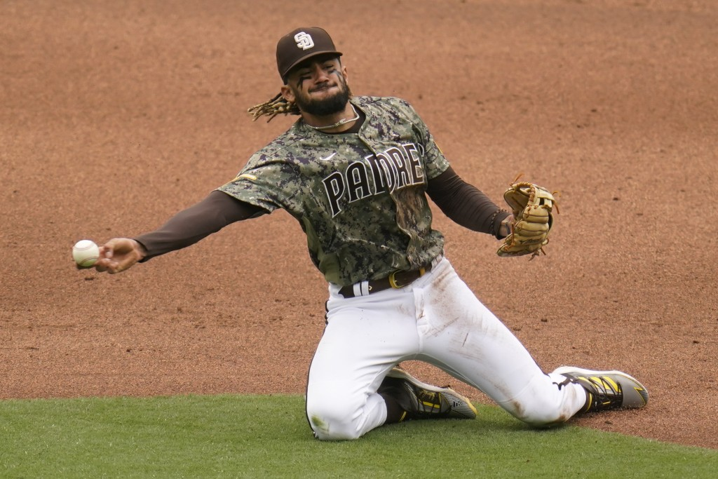 San Diego Padres shortstop Fernando Tatis Jr., throws to first from his knees in time for the out on San Francisco Giants' Wilmer Flores during the fi...