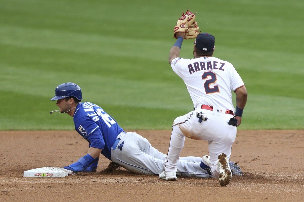 Minnesota Twins second baseman Luis Arraez, right, tags Kansas City Royals' Andrew Benintendi, left, out at second base after trying to steal the base...
