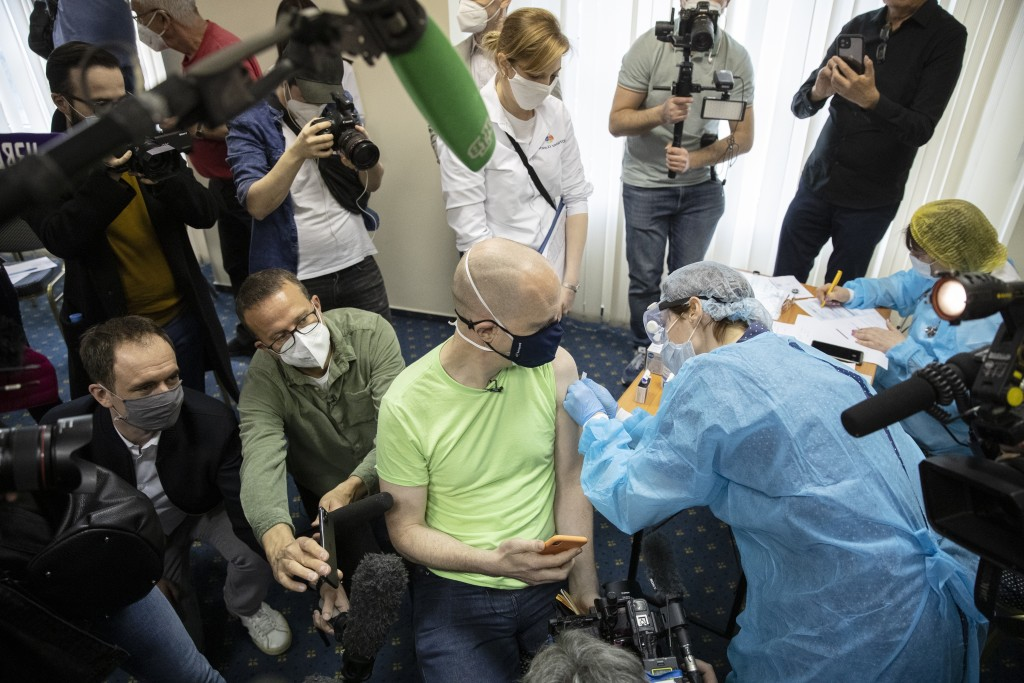 Germany's tourist Uwe Keim, center, wearing a face mask to protect against coronavirus gets the first shot of Russia's Sputnik V coronavirus vaccine i...