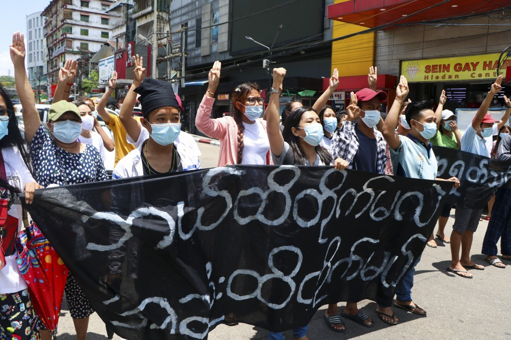Anti-coup protesters flashes the three-finger salute of defiance and chant slogans with banners that read; '' The Kamayut strike will be fight for to ...