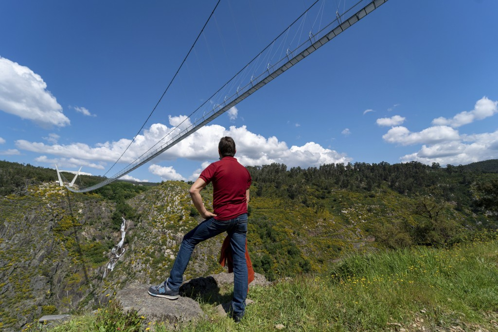 A man looks at a narrow footbridge suspended across a river canyon, which claims to be the world's longest pedestrian bridge, in Arouca, northern Port...