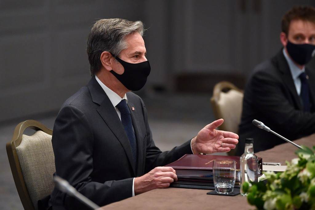 United States Secretary of State Antony Blinken, wearing a face mask to curb the spread of COVID-19, sits at a table for during bilateral talks with J...