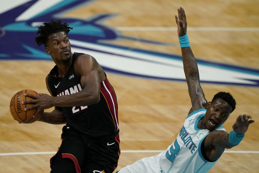 Miami Heat forward Jimmy Butler drives to the basket past Charlotte Hornets guard Terry Rozier during the first half of an NBA basketball game on Sund...