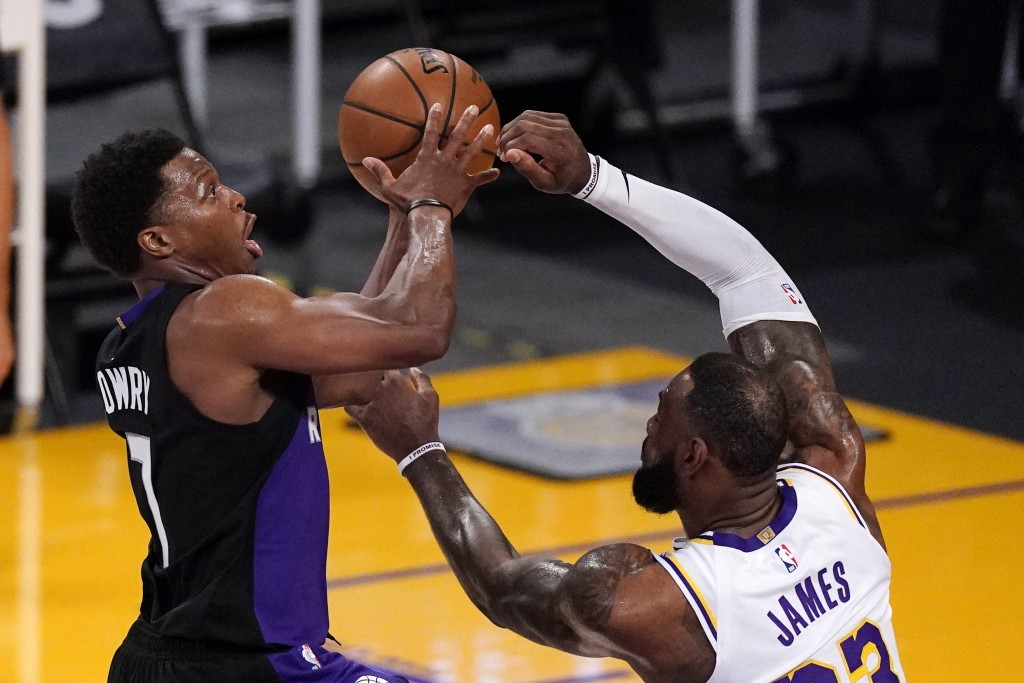 Toronto Raptors guard Kyle Lowry, left, shoots as Los Angeles Lakers forward LeBron James defends during the first half of an NBA basketball game Sund...