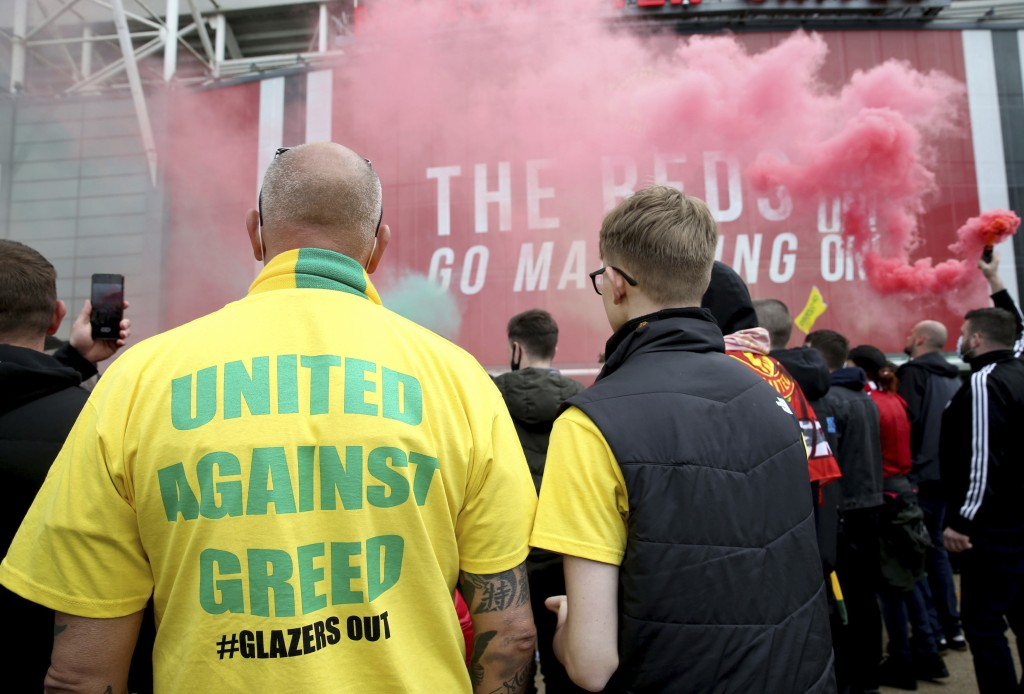 """A fan wears a shirt with a """"United Against Greed"""" message, as fans gather to protest against the Glazer family, the owners of Manchester United, outsi..."""