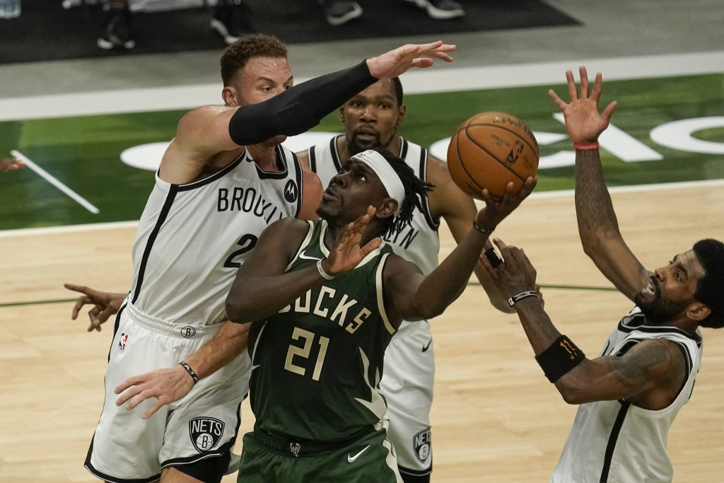 Milwaukee Bucks' Jrue Holiday shoots in traffic during the second half of an NBA basketball game against the Brooklyn Nets Sunday, May 2, 2021, in Mil...