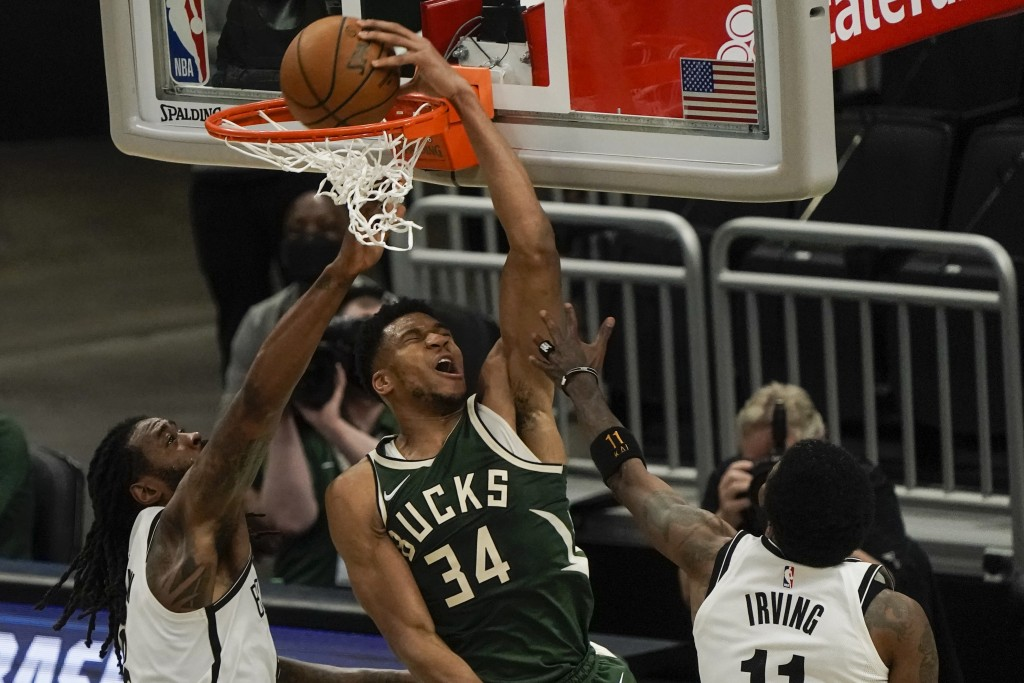Milwaukee Bucks' Giannis Antetokounmpo dunks in front of Brooklyn Nets' DeAndre Jordan during the first half of an NBA basketball game Sunday, May 2, ...