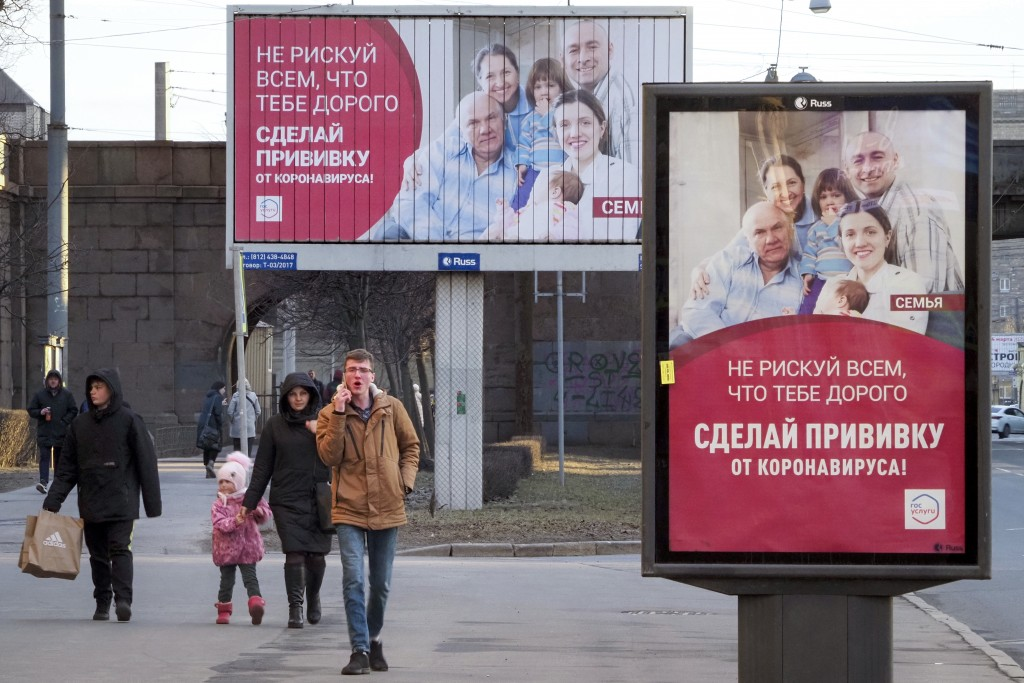 """People walk past posters reading """"Do not risk everything that is dear to you. Get vaccinated against coronavirus"""" in St. Petersburg, Russia, Saturday,..."""