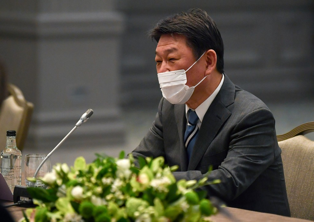 Japan's Foreign Minister Toshimitsu Motegi, wearing a face mask to curb the spread of COVID-19, sits at a table during bilateral talks with United Sta...