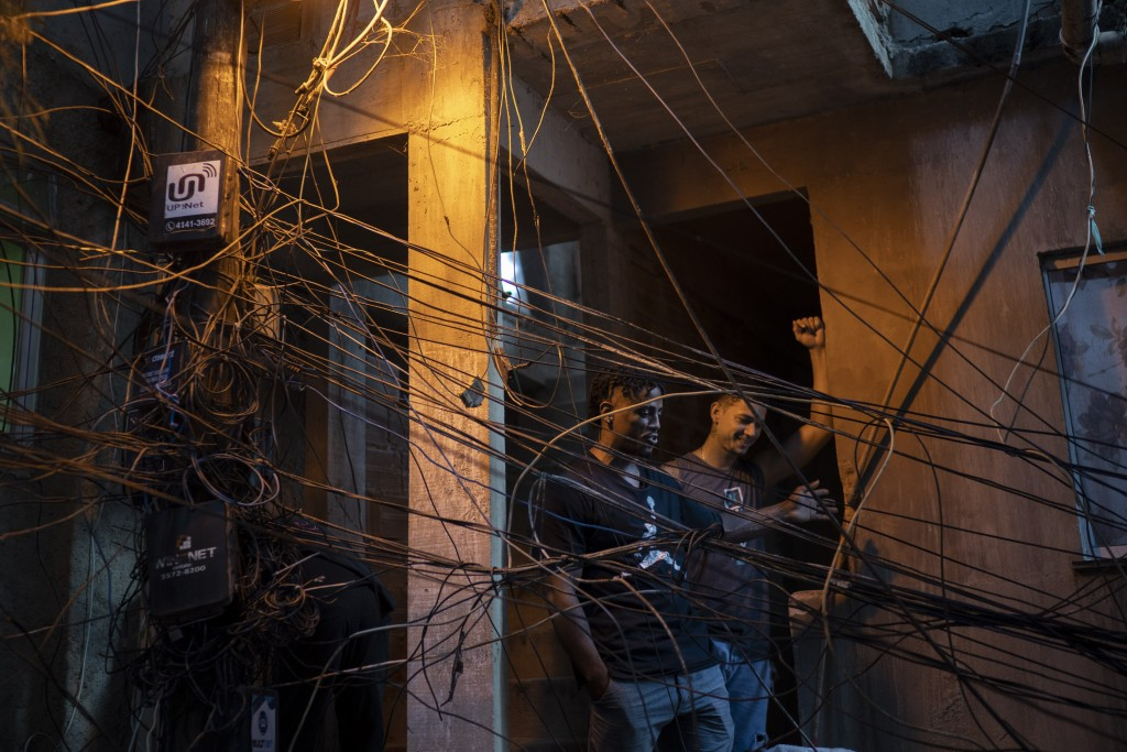 """Trap de Cria artist Vitor Oliveira, known as """"MC Piloto,"""" stands at the entrance of his home and recording studio with Brendon Kelvin, in the Rocinha ..."""