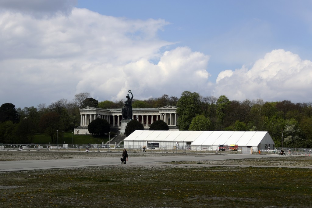 A woman and her dog walk by the 'Oktoberfest' beer festival area 'Theresienwiese' in front of the Bavaria statue and a corona test centre in Munich, G...