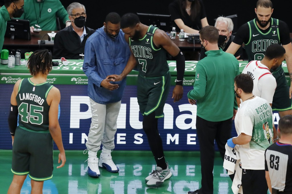 Boston Celtics' Kemba Walker, center left, helps Jaylen Brown (7) after Brown collided with teammate Jayson Tatum during the second half of an NBA bas...