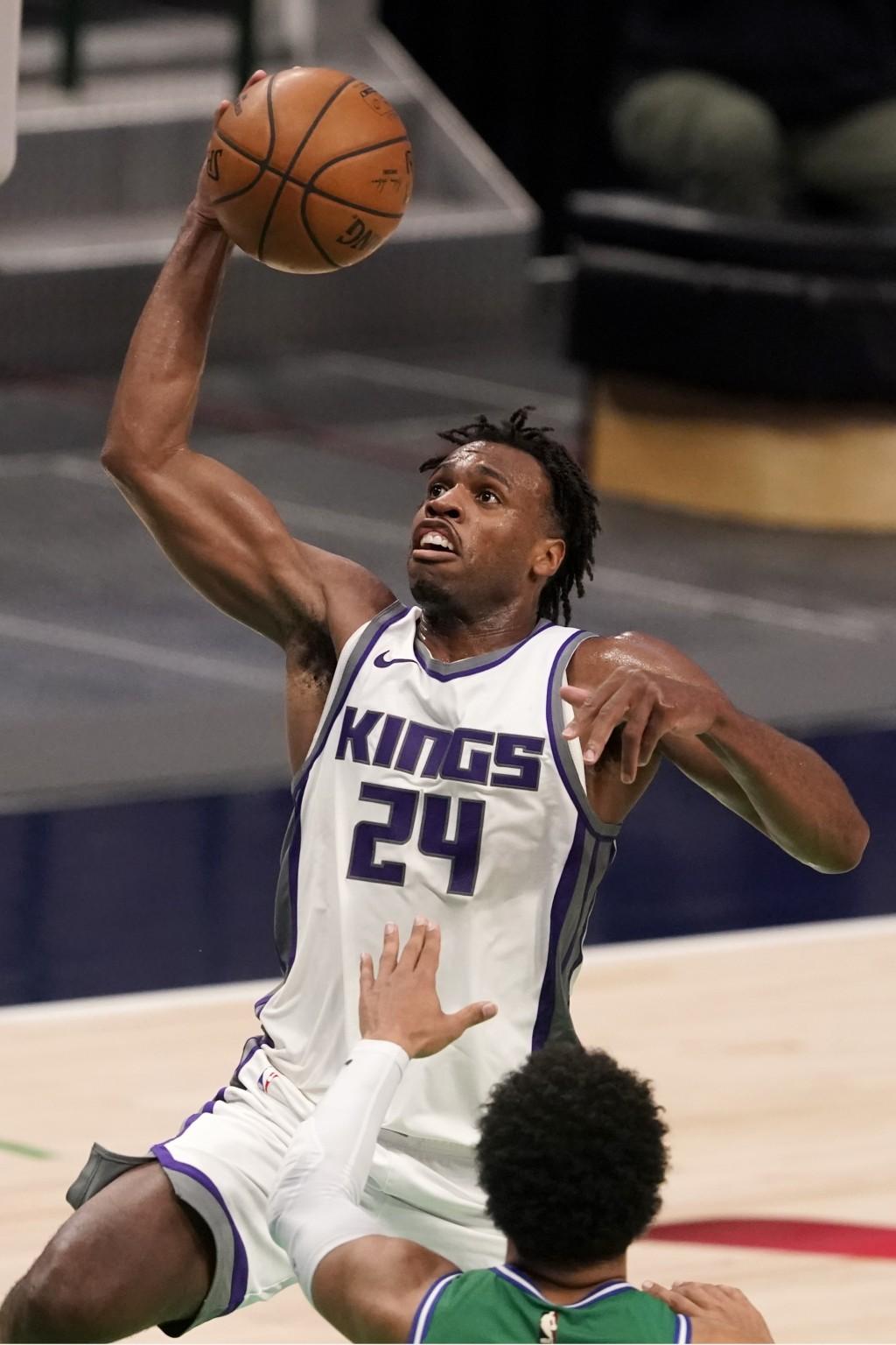 Sacramento Kings guard Buddy Hield (24) goes up for a shot over Dallas Mavericks' Jalen Brunson, bottom, in the second half of an NBA basketball game ...