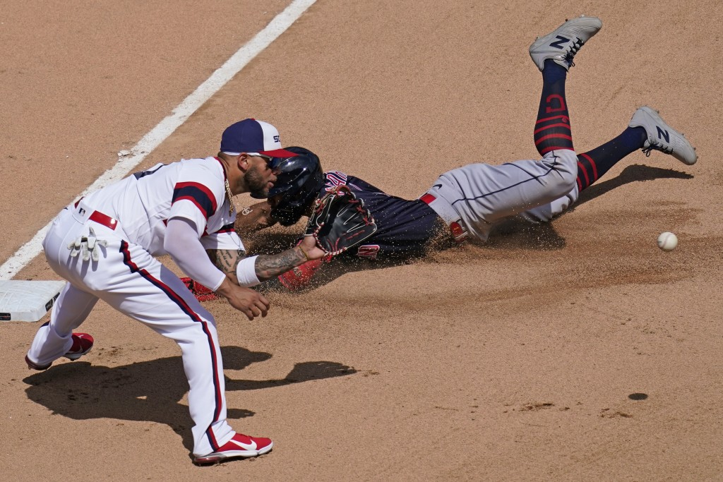 Cleveland Indians' Amed Rosario, right, slides safely into third base after hitting a triple as Chicago White Sox third baseman Yoan Moncada waits for...