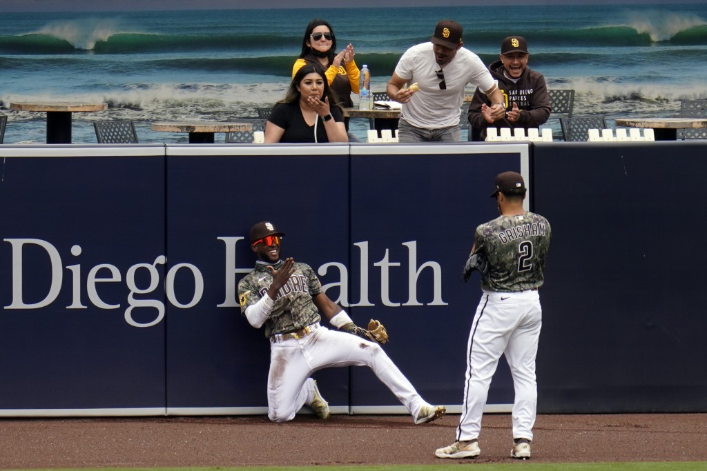 San Diego Padres left fielder Jurickson Profar, below right, reacts with teammate center fielder Trent Grisham after making a catch at the wall for th...