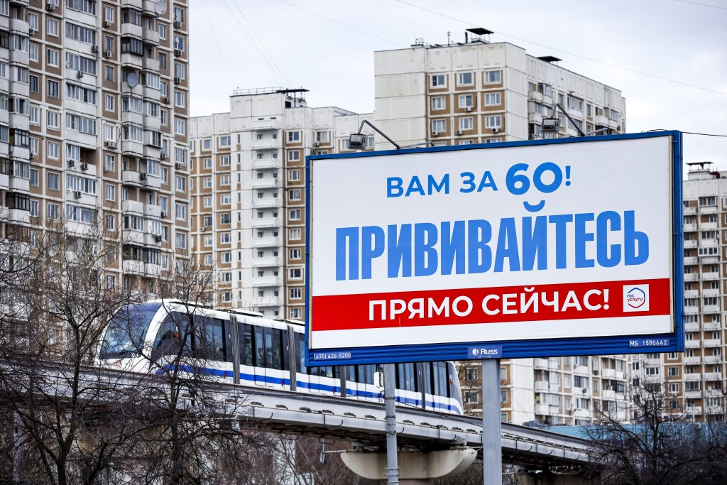 """A monorail car rolls near a gait billboard reading """"You're over 60! Get vaccinated immediately!"""" in Moscow, Russia, Sunday, April 4, 2021. To boost th..."""