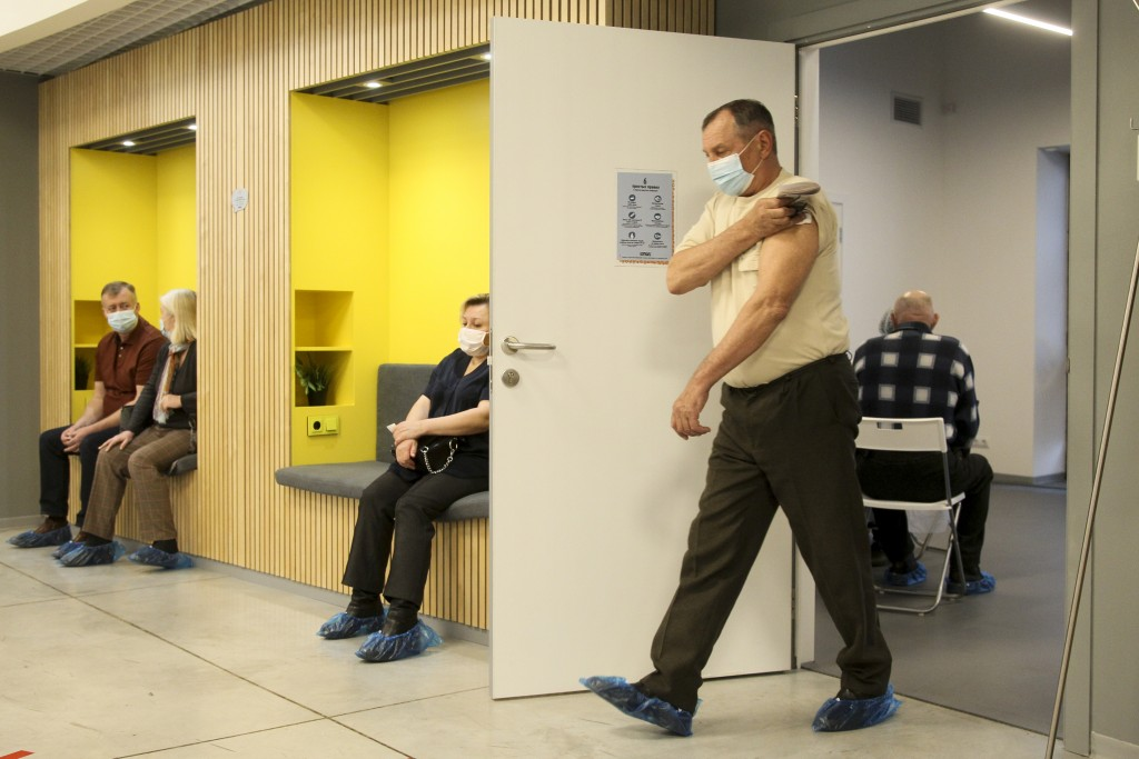 A man wearing a face mask to protect against coronavirus leaves a room after vaccinating with Russia's Sputnik V coronavirus vaccine at a shopping cen...