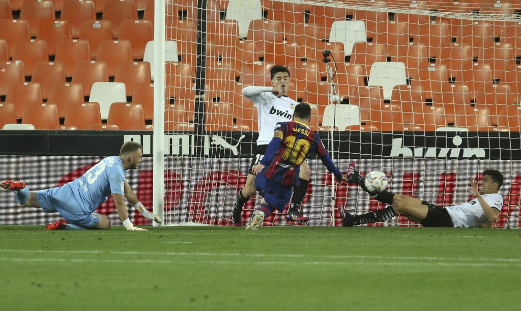 Barcelona's Lionel Messi scores his side's first goal during the Spanish La Liga soccer match between Valencia and Barcelona at the Mestalla stadium i...