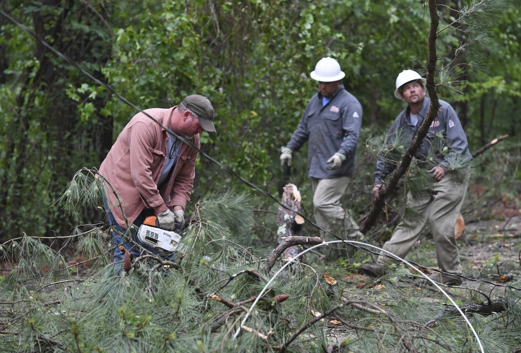 A Tupelo Water and Light crew works to clear downed trees and power lines along Oakview Drive in Tupelo, Miss., Monday, May 3, 2021. A line of severe ...