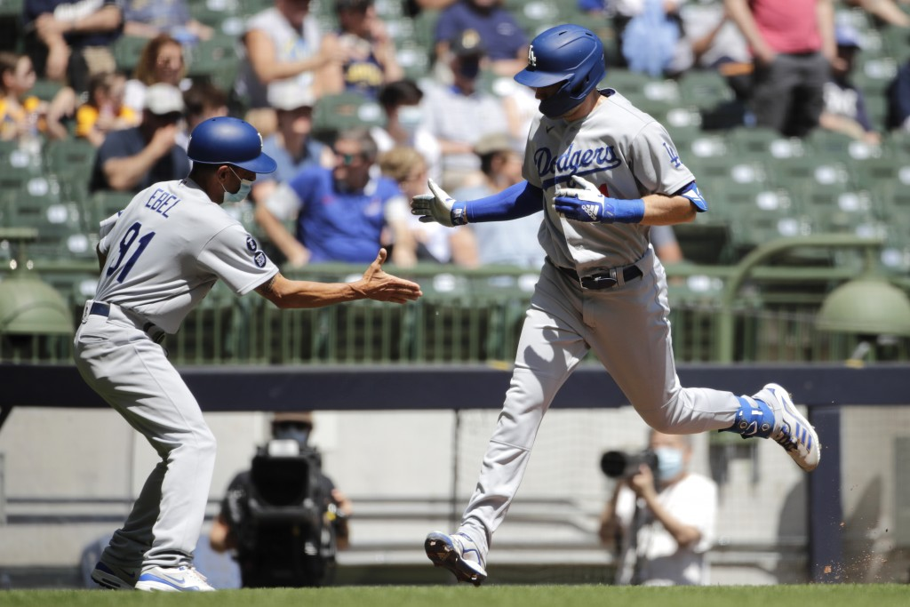 Los Angeles Dodgers' AJ Pollock is congratulated by third base coach Dino Ebel after hitting a home run during the first inning of a baseball game aga...