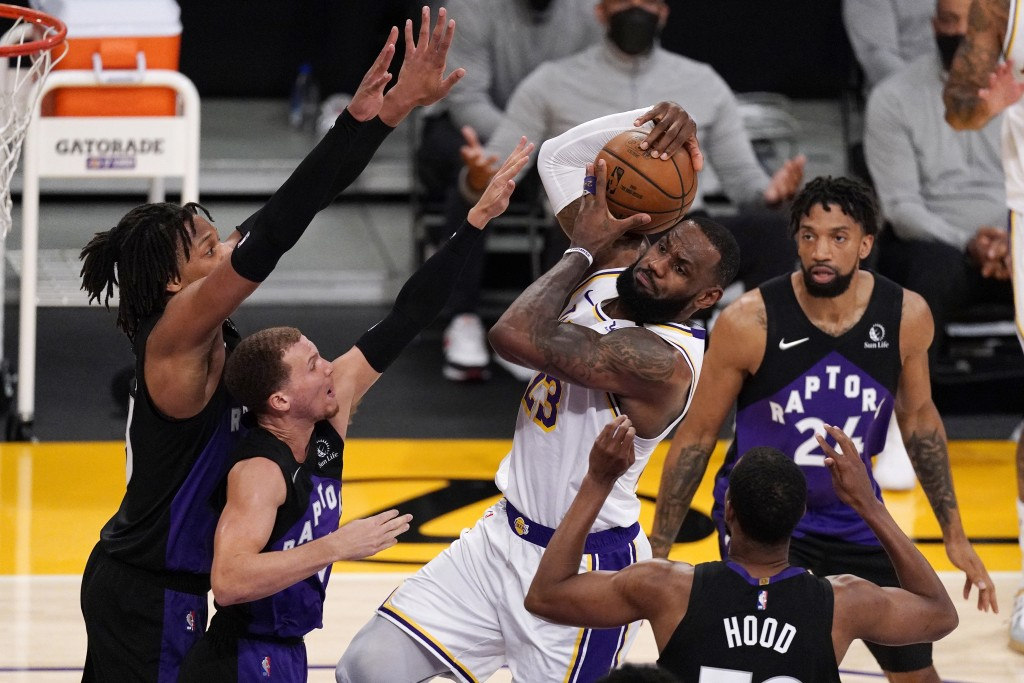 Los Angeles Lakers forward LeBron James, center, tries to shoot as Toronto Raptors forward Freddie Gillespie, left, guard Malachi Flynn, second from l...