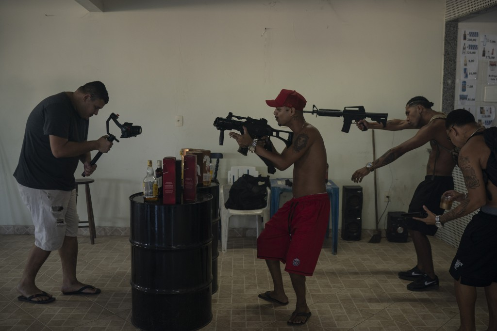 """Trap de Cria artists Marcos Borges, known as """"MbNaVoz,"""" center, Pablo """"PBSant,"""" second right, and Fernando """"Barbeirin,"""" right, hold Airsoft guns as ca..."""