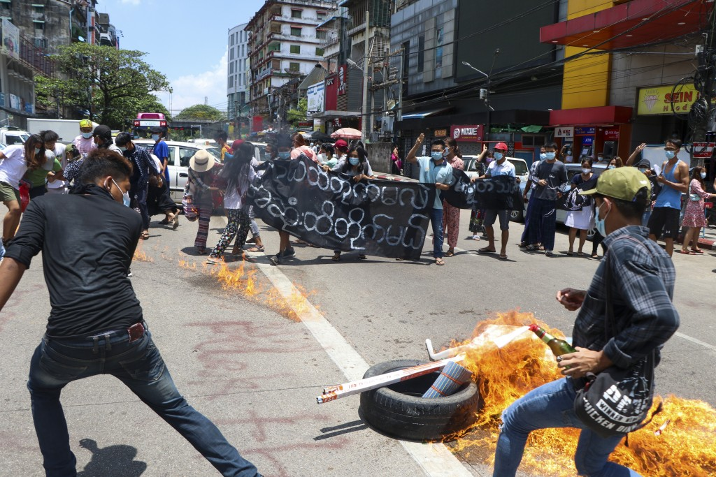 """Anti-coup protesters burn tires and chant slogans with banner read ''The Kamayut strike will be fight for to the end when we get victory"""" during the d..."""