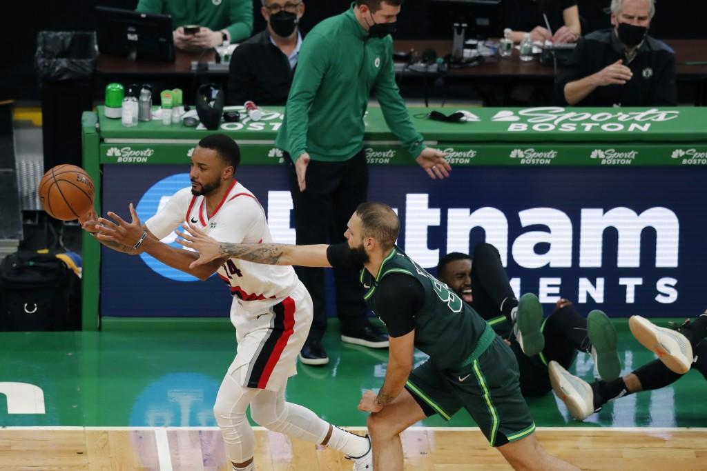 Boston Celtics' Evan Fournier (94) defends against Portland Trail Blazers' Norman Powell (24) as Boston Celtics' Jaylen Brown, behind right, collides ...