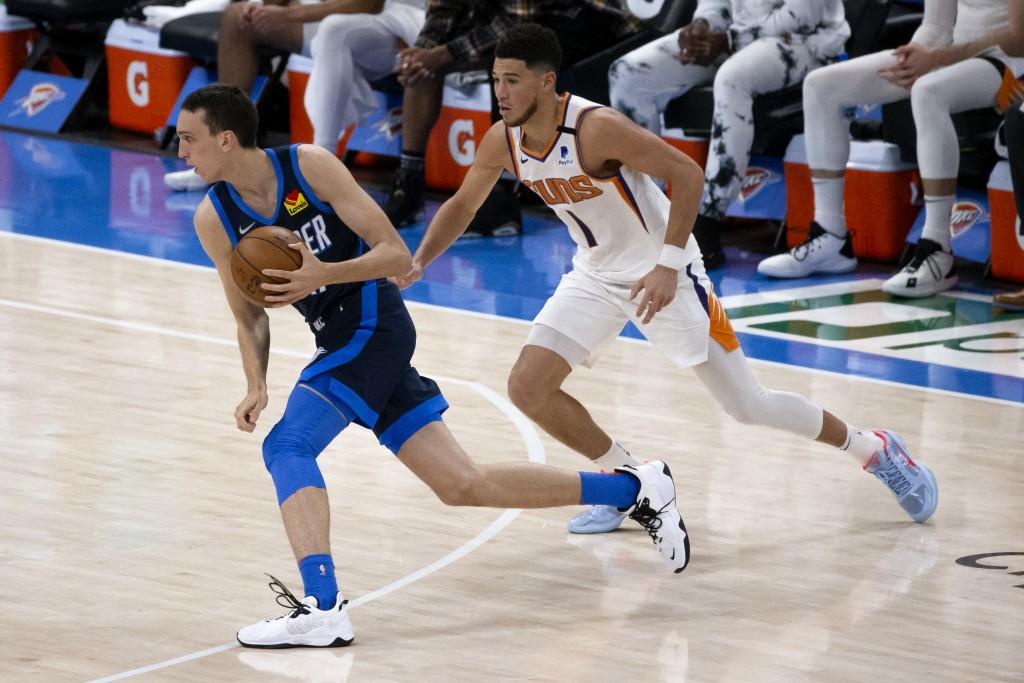 Oklahoma City Thunder forward Aleksej Pokusevski (17) goes against Phoenix Suns guard Devin Booker (1) during the first half of an NBA basketball game...
