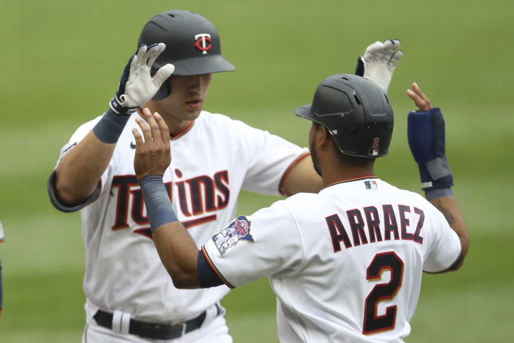 Minnesota Twins' Alex Kirilloff, left, high-fives teammate Luis Arraez (2) after hitting a home run in the eighth inning of a baseball game against th...