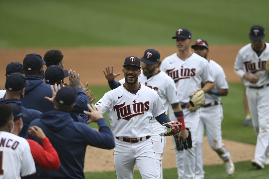 Minnesota Twins' Byron Buxton, center, smiles as he high-fives teammates after defeating the Kansas City Royals in a baseball game Sunday, May 2, 2021...